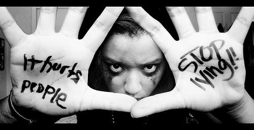 Girl with stop lying written on her palms