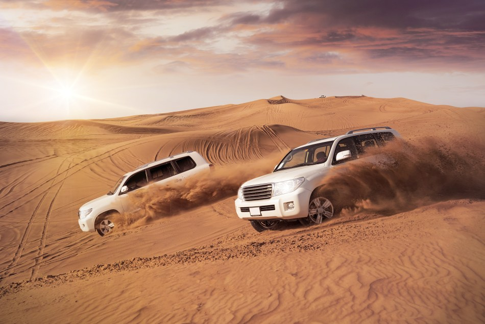 Two 4WD vehicles driving over sand dunes in the Dubai Desert