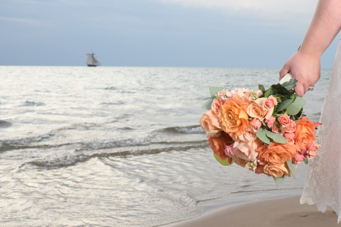 brides bouquet with sail boat in background