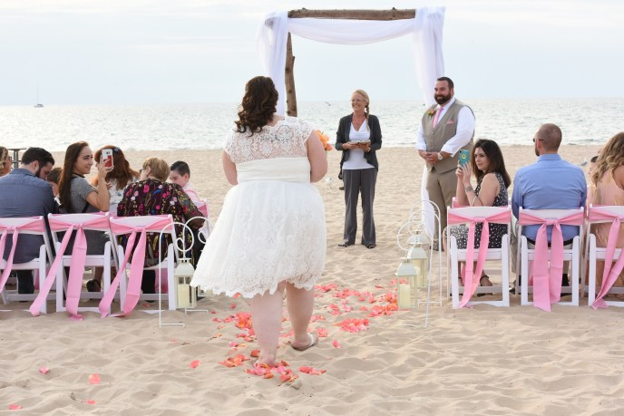 bride walks down an asile of sand