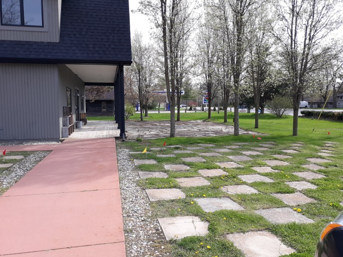 Tree lined slate patio in front of main barn