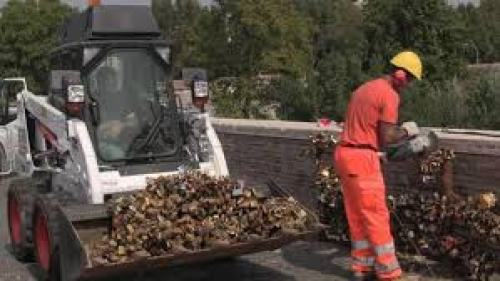 The enormity of the problem - a bulldozer being loaded with lovelocks removed from a bridge