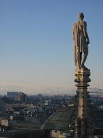 A statue stands precariously atop one of Milan Duomo's spindly spires
