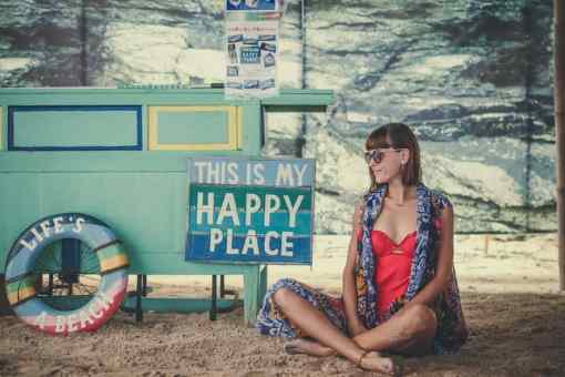 woman siting next to happy place sign
