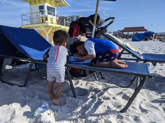 Two Kids playing on  beach lounge chairs at clear water beach
