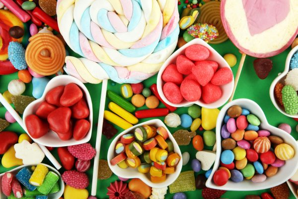 candies with jelly and sugar. colorful array of different childs sweets and treats on green