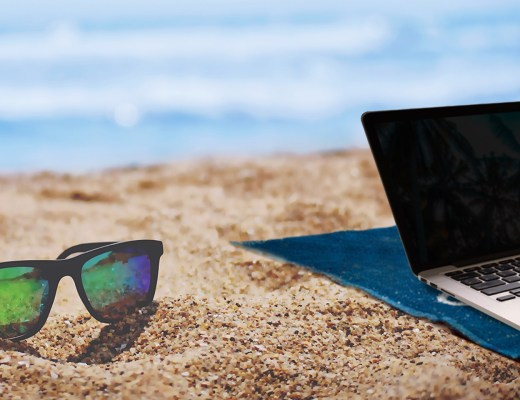 sunglasses and laptop with the ocean in the background