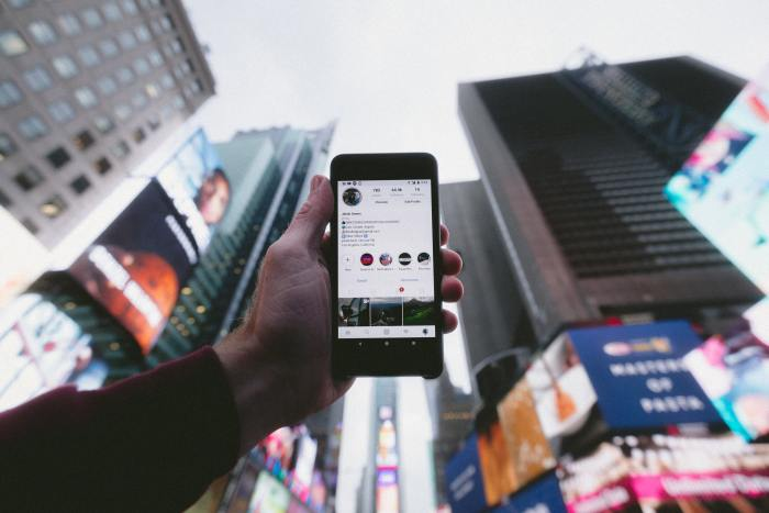 man holding phone looking at instagram