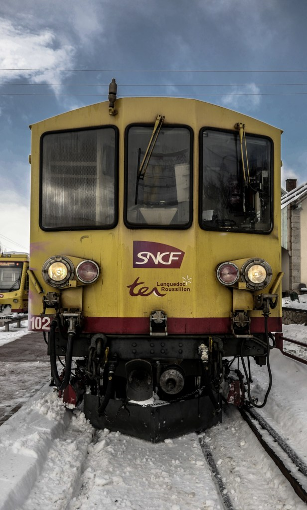 The electric locomotive of the yellow train, a french heritage, during typical journey of winter, in the Pyrenees Orientales, region of southwest of France.La locomotive electrique du train jaune, un patrimoine francais, durant un trajet typique d hiver, dans les Pyrenees Orientaes, region du sud ouest de la France.