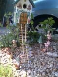 The Fairy house the blue flowers are making their home up the ladder