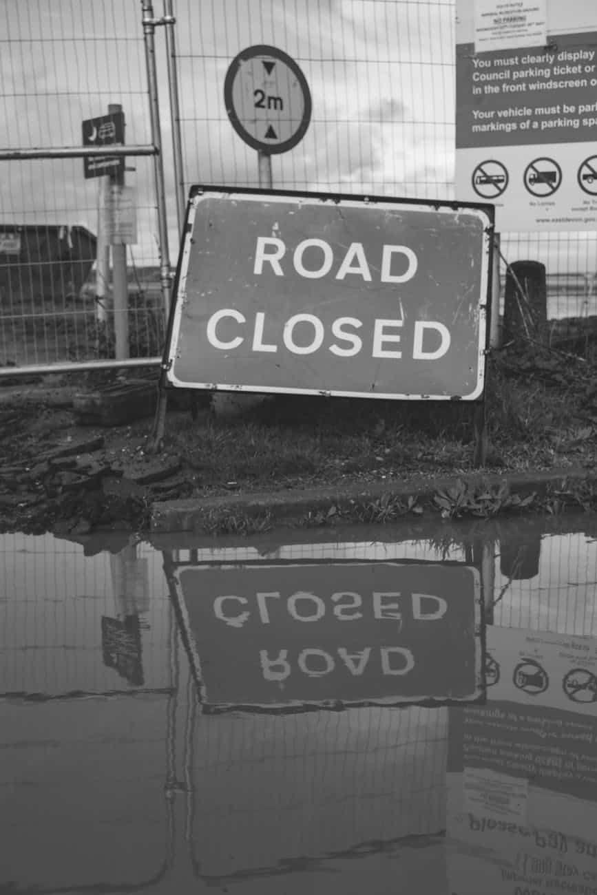 grayscale photo of road closed