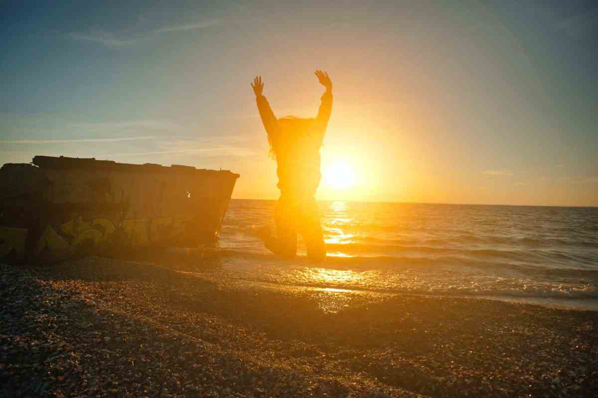 person jumping on seashore during golden hour