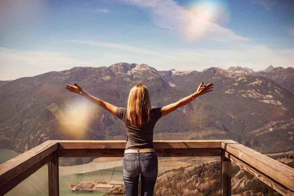 woman facing mountains raising her hands