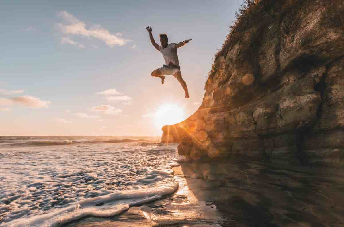 man jumps from cliff to water The Frequency of Love