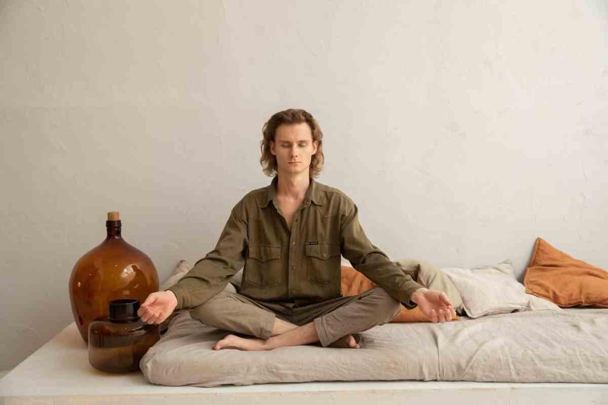 serene man meditating in lotus pose on sofa Power of Meditation