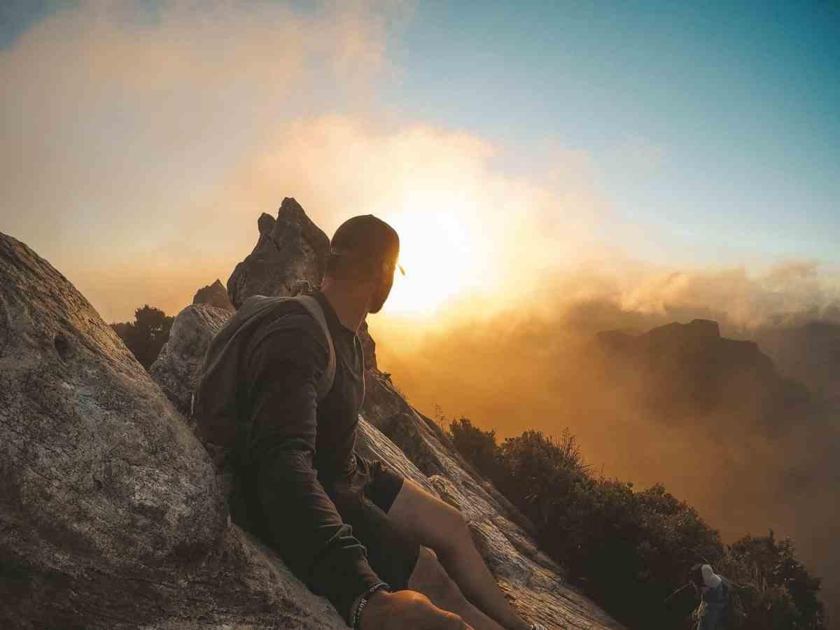 man wearing black long sleeved shirt standing on mountain - micro-shifting can help you achieve abundance