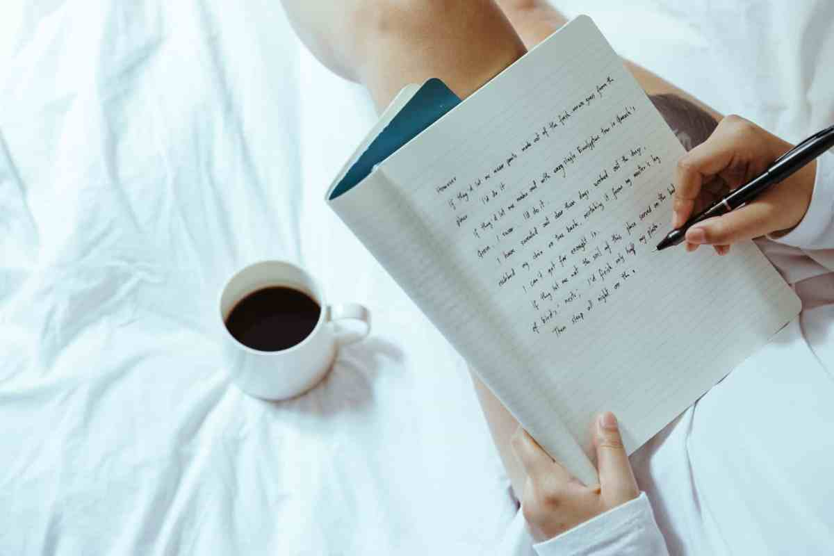 crop woman with coffee writing in notebook on bed - dream with your eyes open