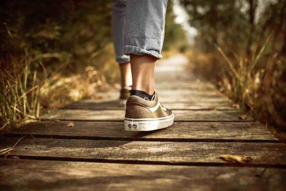 person stands on brown pathway - meditation and how it can help you