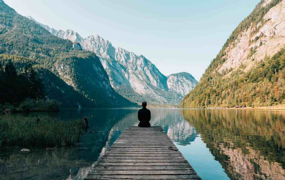 person on a bridge near a lake - why you should stop meditating