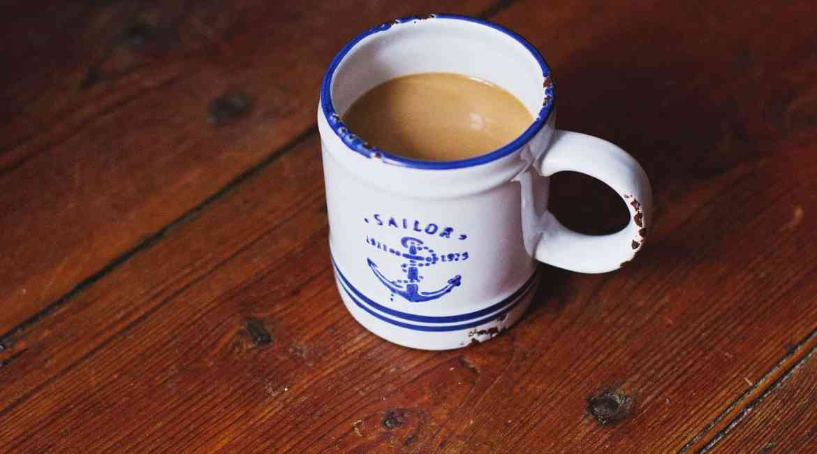 white and blue sailor ceramic coffee mug on brown wooden surface