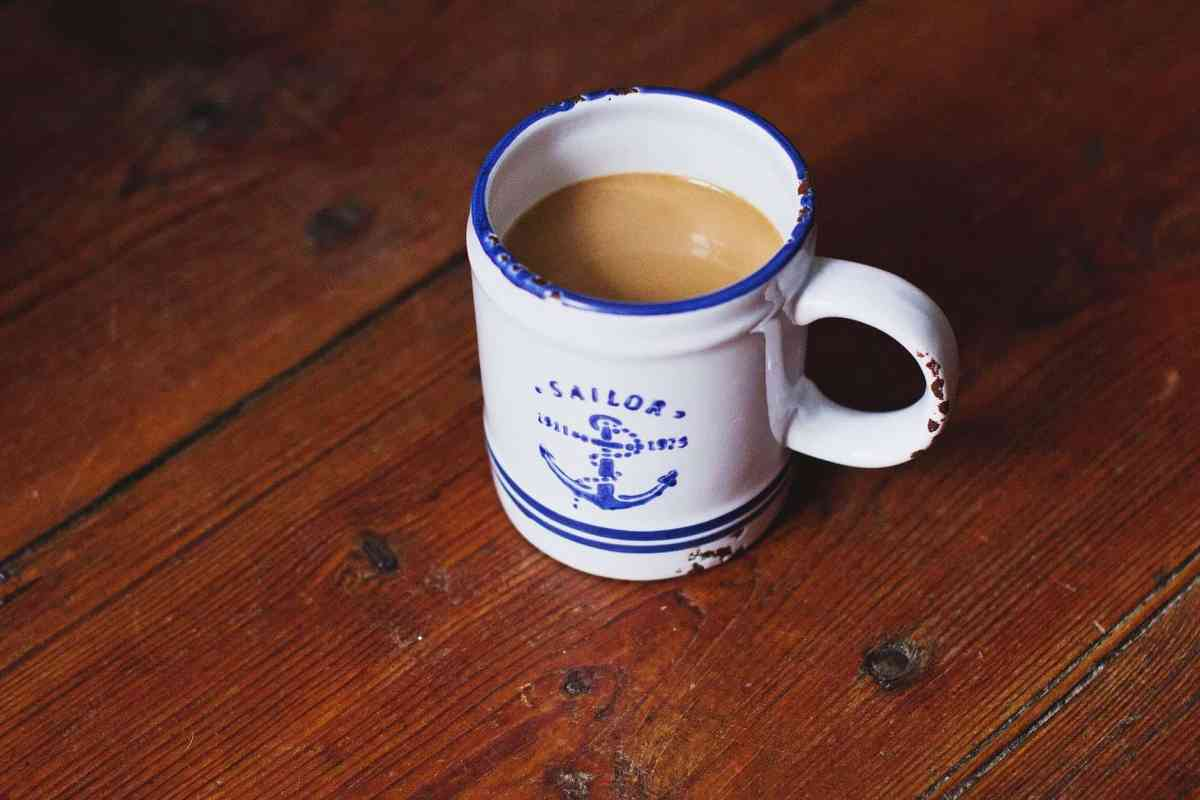 white and blue sailor ceramic coffee mug on brown wooden surface - change in your physical reality