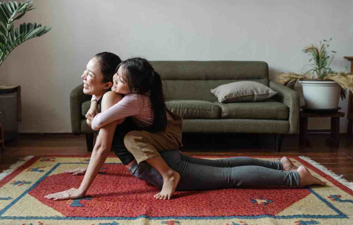 photo of girl hugging her mom while doing yoga pose - consistency is key