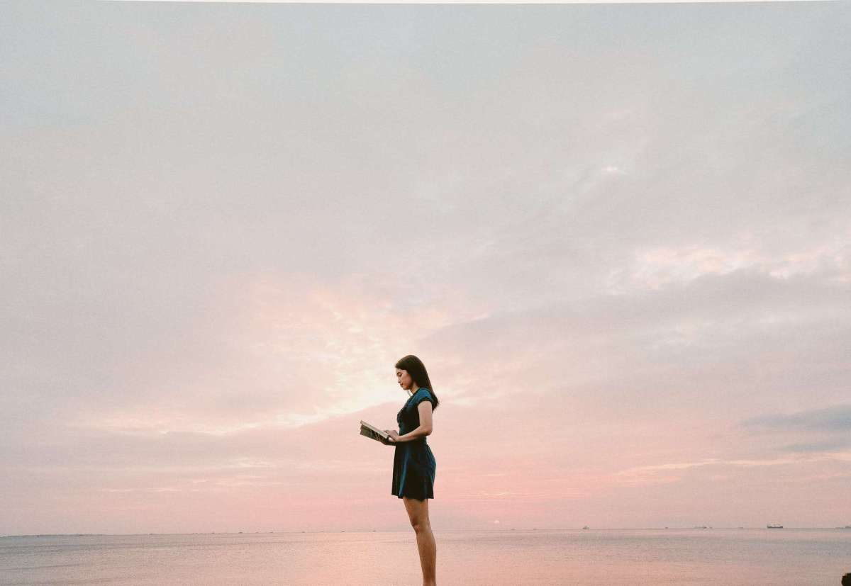 woman wearing black dress standing and reading book -microshifting can help you get manifesting