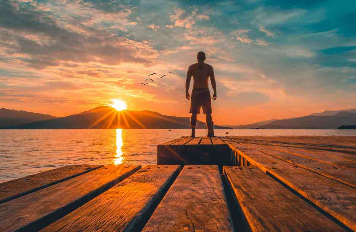 photo of man standing on wooden planks near sea - power of meditation to manifest your dreams