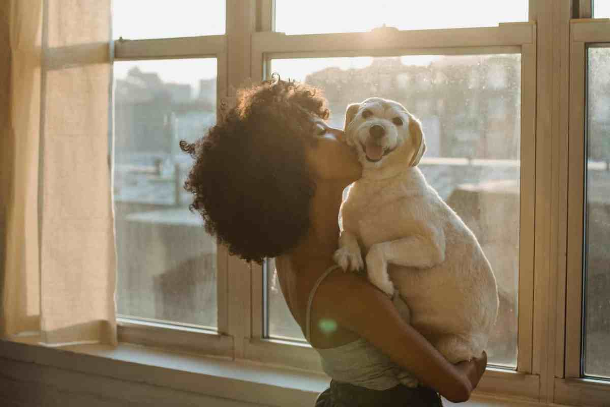 black woman kissing cute purebred dog - power of meditation to manifest your dreams
