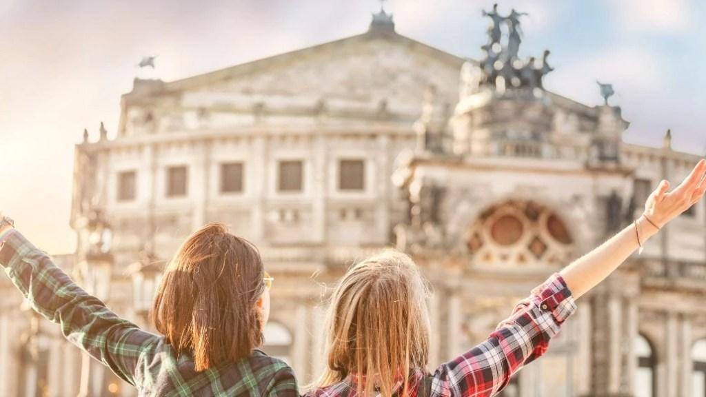 zwei junge Frauen stehen vor der Semperoper in Dresden und stecken die Arme in die Luft