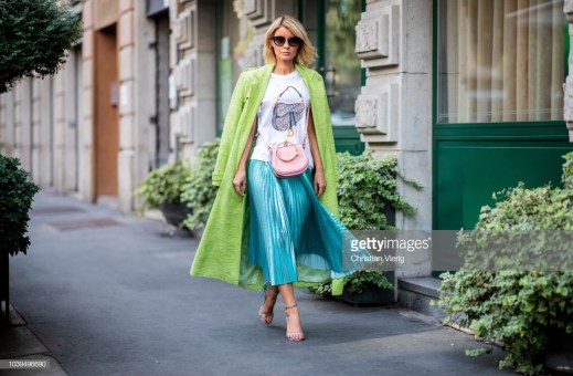 MILAN, ITALY - SEPTEMBER 22: Gitta Banko wearing a neon green coat by Danny Reinke, white t-shirt with saddle bag print by Wodka Ogurez, shiny green pleated skirt by Dawid Tomaszewski, Chiara sandals by Sophia Webster, soft pink Nile bag by Chloe and sunglasses by Chanel during Milan Fashion Week Spring/Summer 2019 on September 22, 2018 in Milan, Italy. (Photo by Christian Vierig/Getty Images)