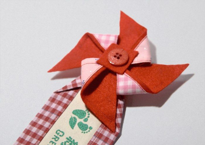 Green Baby Garden CNY edition uniform brooch with a red pinwheel