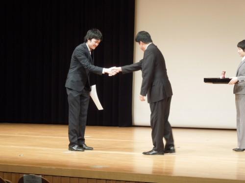 学生支援センター所長から表彰状と盾を受け取る大垣2013年度会長