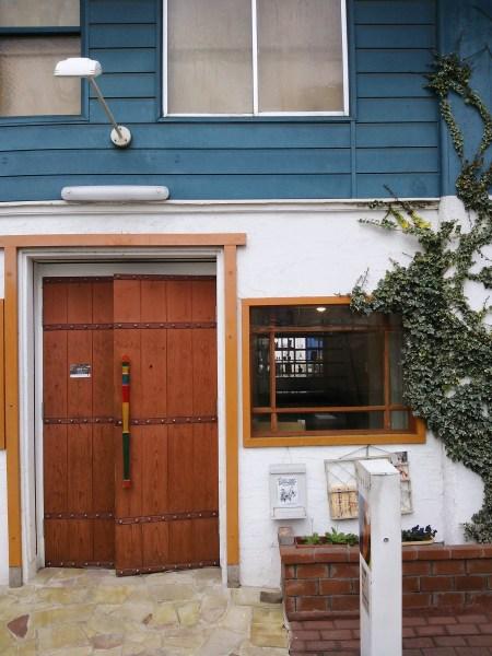 この扉からお入り頂き、階段を上がってください。階段上がって右側が、本展示が行われている会場です。