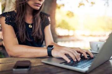 Young woman working on her laptop while wearing a smart watch