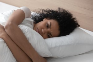 woman sad laying in bed