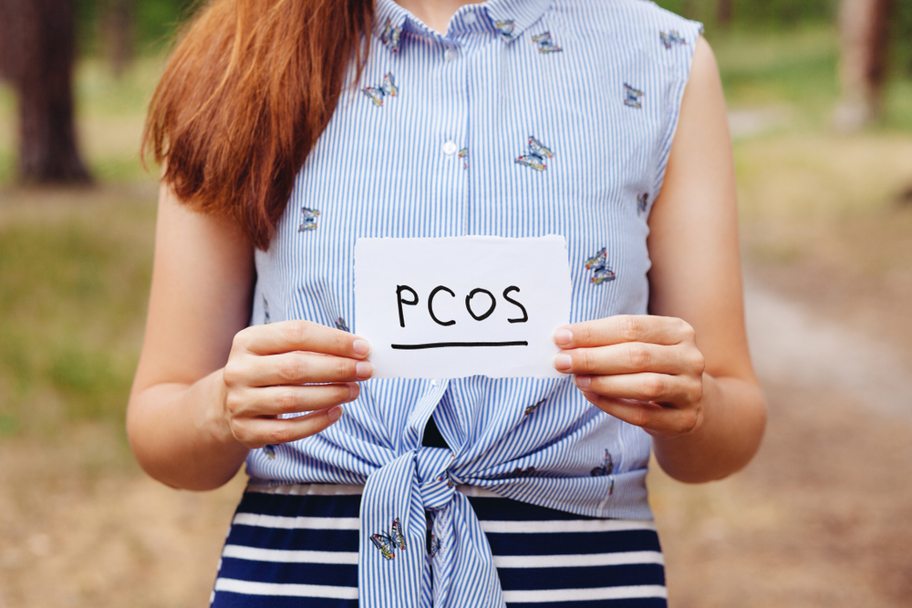 woman holding paper with pcos written on it