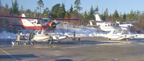"""In the Early morning snow, with no place else to go."" The flight line-up at Bella Bella. a gorgeous Beaver and a Cessna Caravan on amphib. floats."