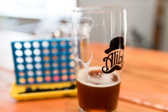A tiny game of Connect Four with a pint of Alibi Ale Works beer. Photo by Mike Higdon