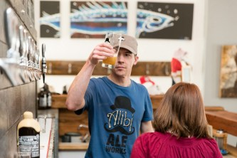 Kevin Drake, owner of Alibi Ale Works, checks the quality of the first pour of pale ale in February.e