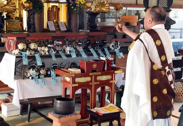 Kofuku-ji temple chief priest Bungen Oi (R) offers a prayer during the funeral for 19 Sony's pet robot AIBOs, in Isumi, Japan's Chiba prefecture ©Toshifumi Kitamura (AFP) [Courtesy Daily Mail]