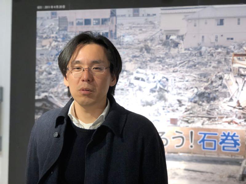 みらいサポート石巻専務理事、中川政治さん。初代の「がんばろう!石巻」看板の写真の前で。