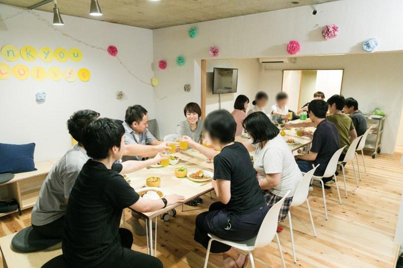 コミュニティスペースで一緒に食事をとる参加者