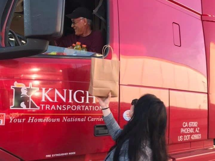 Volunteer handing Knight Transportation driver food through truck window