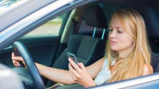 Young woman writing sms while driving - Photo copyright: dmitrimaruta