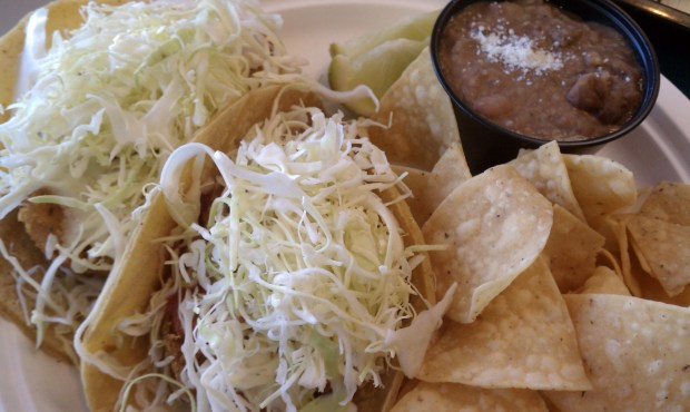Rubio's fish tacos served with chips and beans.