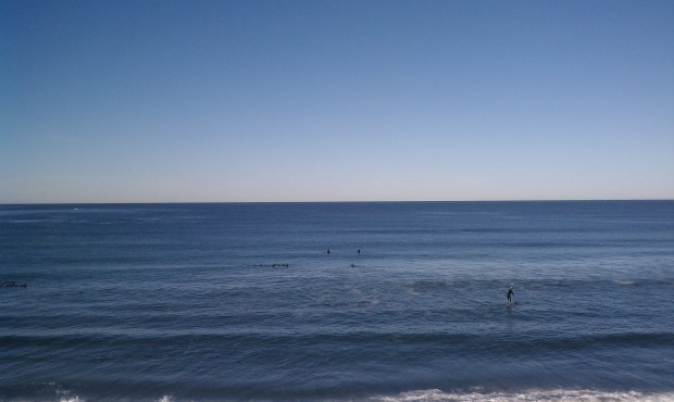 Surfing: a jog to the beach in funny clothing, a stretch, and a patient soak in the water waiting for a wave.