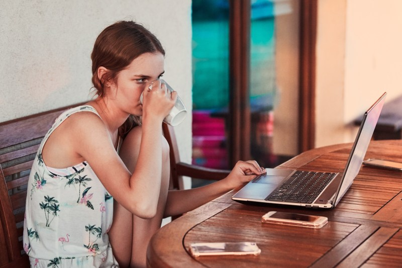 woman-working-at-home-using-portable-computer-sitting-on-patio-on-summer-day-candid-people-real_t20_NxbYkN