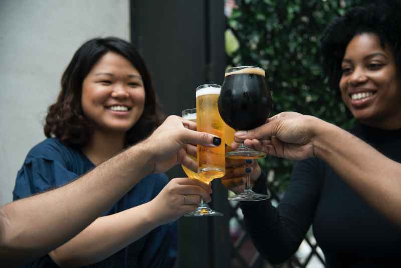 women holding glasses having toasting