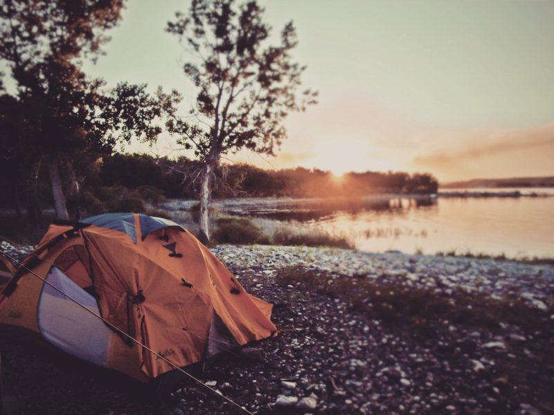 Orange tent pitched next to Lake Tahoe.